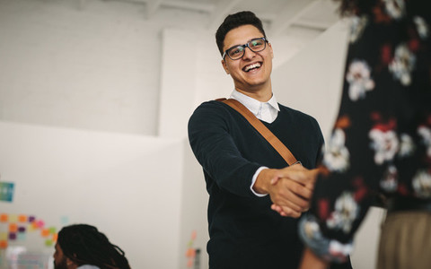Smiling businessman greeting a business partner at work