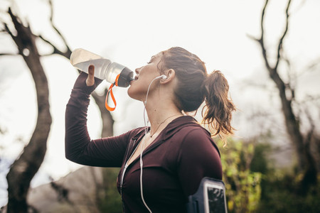 Woman drinking water after a running exercise