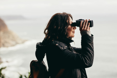 Female hiker enjoying spectacular view through binoculars