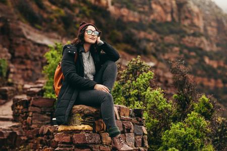 Female traveler relaxing at the hillside admiring the view