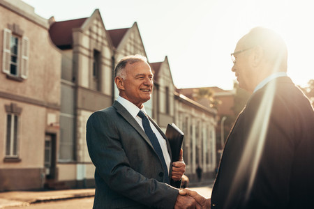 Two business partners handshake outdoors