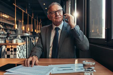 Confident senior businessman at coffee shop using phone