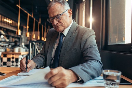 Senior businessman sitting at cafe and working