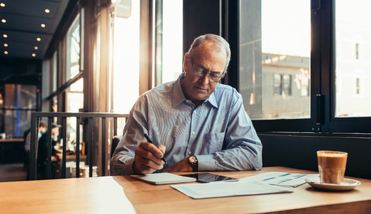 Mature businessman in cafe making notes