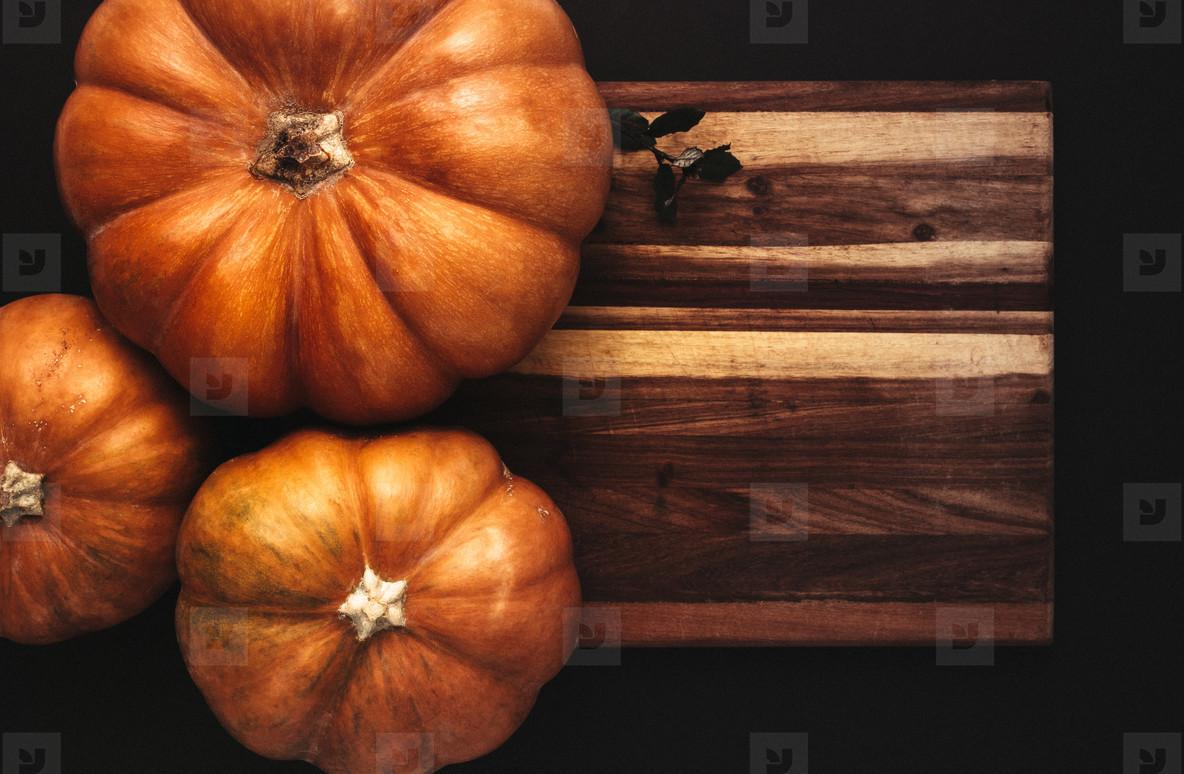 Halloween flat lay of pumpkins on wooden board