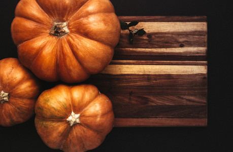 Halloween flat lay of pumpkins on wooden board