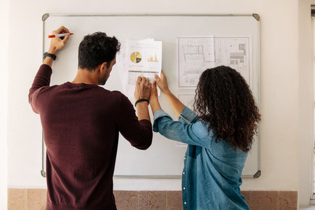 Business partners discussing work on a whiteboard in office