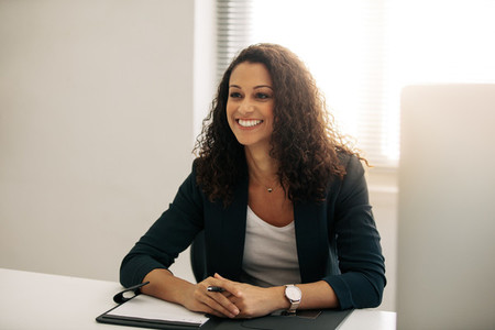 Smiling businesswoman sitting at her desk in office