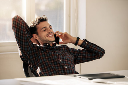 Businessman talking over mobile phone in office
