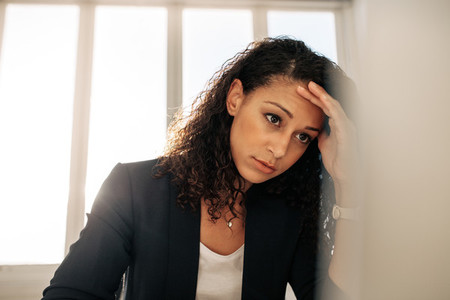 Woman entrepreneur sitting in office holding her head