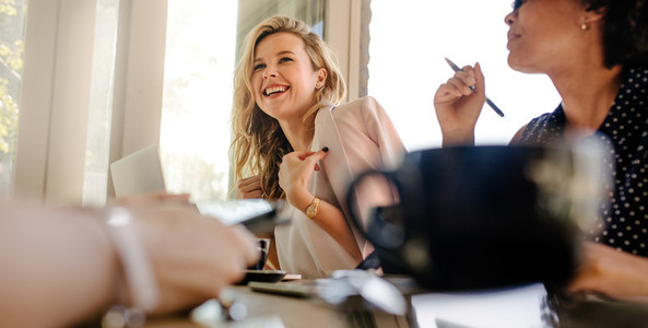 Smiling woman in meeting with colleagues