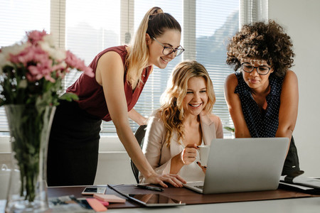 Three businesswomen looking at laptop and smiling