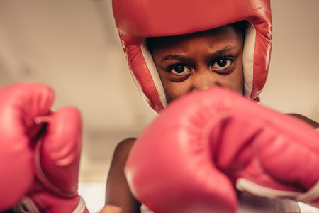 Close up of kid in boxing gloves and head guard
