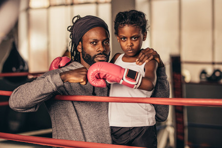 Boxing trainer with a kid boxer standing inside a boxing ring
