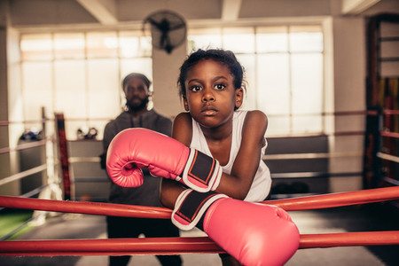 Girl wearing boxing gloves standing near a boxing ring