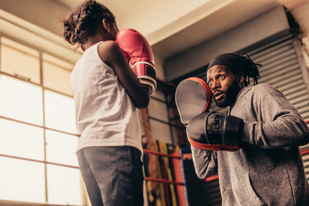 Low angle view of a boxing girl training with her coach