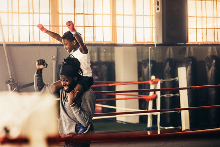Kid sitting on shoulders of boxing coach celebrating a win