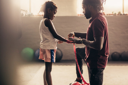 Boxing trainer wrapping hands of a kid with bandage