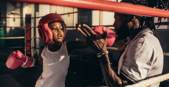 Kid learning boxing from his coach in a boxing ring