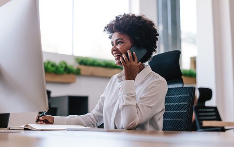 Smiling businesswoman talking with client over phone