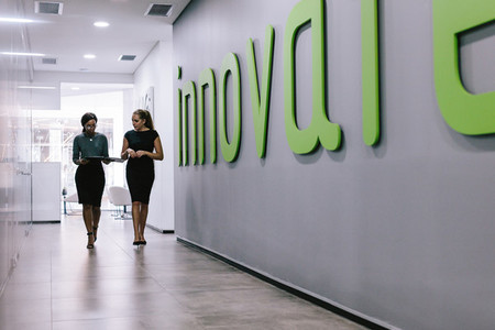 Female coworkers walking in office corridor