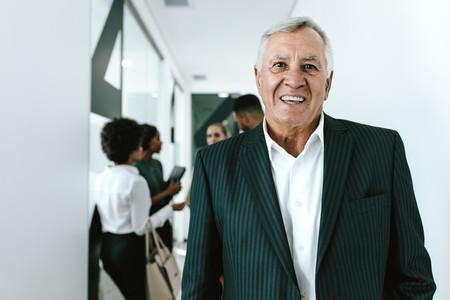 Happy senior businessman in office corridor