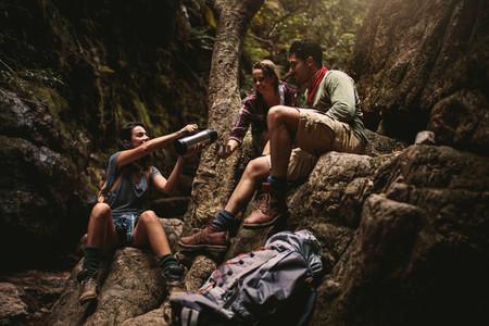 Friends taking coffee break while hiking in rocky mountain