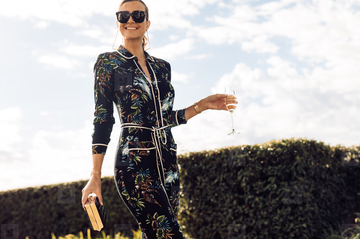 Stylish woman walking with glass of wine