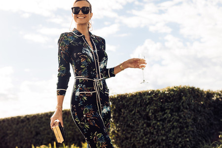 Stylish woman walking with glass of wine