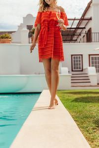 Woman in beautiful dress walking by pool