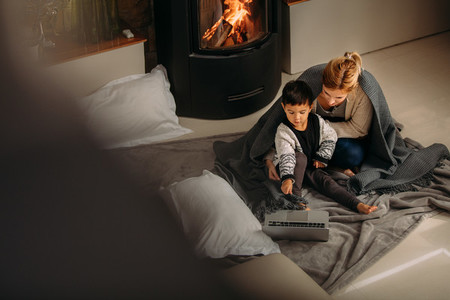 Mother and son with laptop near fireplace