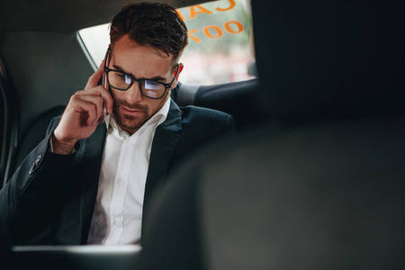 Businessman talking on mobile phone sitting in a taxi