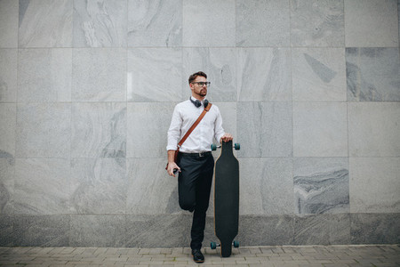 Businessman standing in street holding a longboard