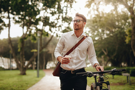 Man enjoying coffee and music while walking to office