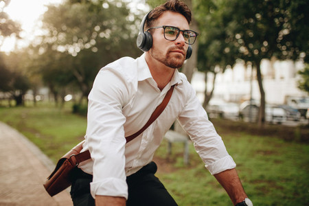Man going to office on a bicycle listening to music