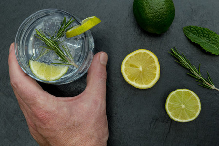 Hand holding glass of gin tonic with ice and lime dark backgroun