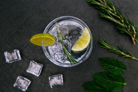 Gin tonic cocktail drink with ice glass dark background