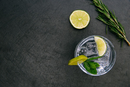 Gin tonic cocktail drink with ice glass green lime dark backgrou