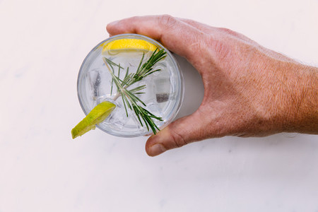 Hand holding glass of gin tonic with ice and lime white backgrou