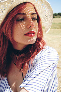 Young redhead woman covering from sun