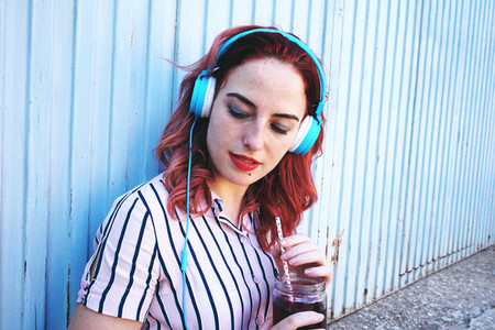 Beautiful redhead woman listening to music