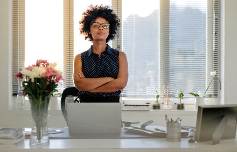 Confident young businesswoman standing at her desk