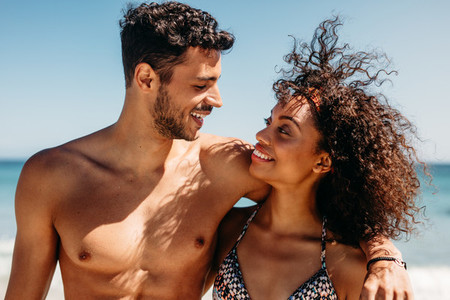 Close up of romantic couple on the beach looking at each other
