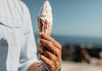 Close up of a man holding a cone ice cream