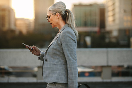 Businesswoman using smart phone on city street