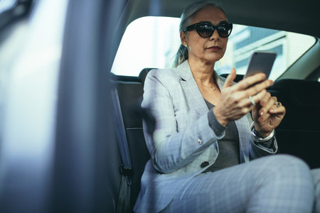 Senior businesswoman traveling by a car using smart phone