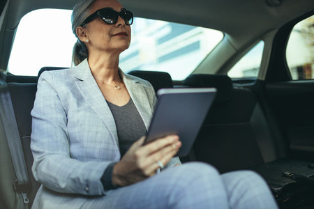 Senior businesswoman in car with tablet pc