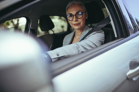 Senior businesswoman going to office in her car