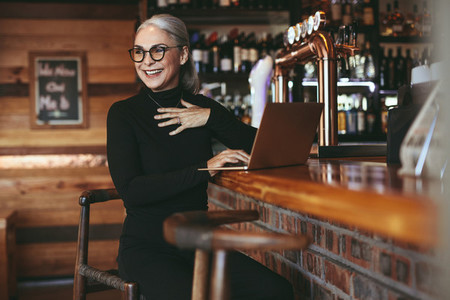 Senior businesswoman sitting at cafe counter with laptop