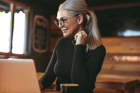 Beautiful senior woman at cafe using laptop computer